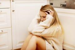 Giovane donna sola triste che si siede nella cucina Immagini Stock