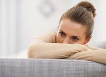 Giovane donna sollecitata che si siede sul sofà fotografia stock