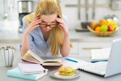 Giovane donna sollecitata che studia nella cucina Fotografia Stock