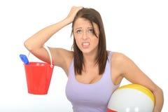 Giovane donna sollecitata frustrata in vacanza che tiene un secchio e un beach ball Fotografie Stock