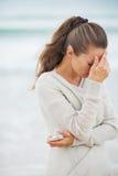 Giovane donna sollecitata in maglione sulla spiaggia con il telefono cellulare Immagini Stock Libere da Diritti