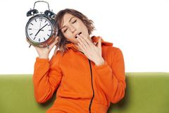 Giovane donna sonnolenta con gli occhi chiusi in vestiti domestici che tengono grande sveglia immagine stock