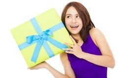 Giovane donna sorpresa che tiene un contenitore di regalo Immagini Stock