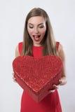 Giovane donna sorpresa che tiene un grande San Valentino del presente del cuore Fotografia Stock
