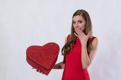 Giovane donna sorpresa che tiene un grande San Valentino del presente del cuore Immagini Stock