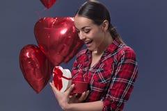 Giovane donna sorpresa con un regalo per il giorno del ` s del biglietto di S. Valentino Fotografia Stock Libera da Diritti