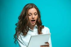 Giovane donna sorpresa di affari con la compressa per le note su fondo blu Fotografia Stock Libera da Diritti