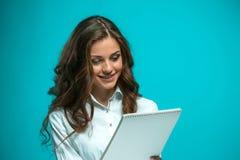 Giovane donna sorpresa di affari con la compressa per le note su fondo blu Fotografie Stock Libere da Diritti