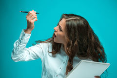 Giovane donna sorpresa di affari con la penna e compressa per le note su fondo blu Immagine Stock