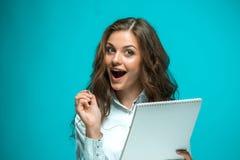 Giovane donna sorpresa di affari con la penna e compressa per le note su fondo blu Immagine Stock Libera da Diritti