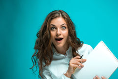 Giovane donna sorpresa di affari con la penna e compressa per le note su fondo blu Fotografia Stock Libera da Diritti