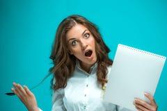 Giovane donna sorpresa di affari con la penna e compressa per le note su fondo blu Fotografie Stock Libere da Diritti