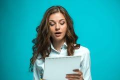Giovane donna sorpresa di affari con la penna e compressa per le note su fondo blu Immagini Stock Libere da Diritti