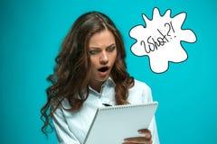 Giovane donna sorpresa di affari con la penna e compressa per le note su fondo blu Fotografia Stock