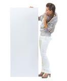 Giovane donna sorpresa in maglione che considera tabellone per le affissioni in bianco Fotografie Stock Libere da Diritti