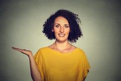 Giovane donna sorridente abbastanza sicura felice che gesturing presentando spazio alla sinistra Fotografia Stock Libera da Diritti