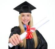 Giovane donna sorridente in abito di graduazione che mostra diploma Immagini Stock Libere da Diritti