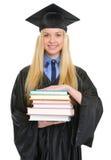 Donna in abito di graduazione con la pila di libri Immagine Stock