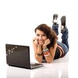 Giovane donna sorridente allegra sveglia che si trova e che studing con il noteboo Fotografia Stock