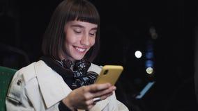 Giovane donna sorridente attraente nel trasporto pubblico facendo uso di un telefono cellulare È mandare un sms, controllante le  video d archivio