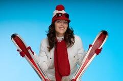 Giovane donna sorridente in attrezzatura rossa e bianca di corsa con gli sci Immagini Stock