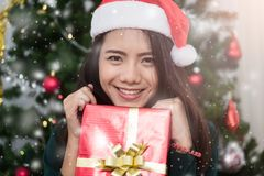 Giovane donna sorridente in cappello dell'assistente di Santa con il contenitore di regalo fotografia stock