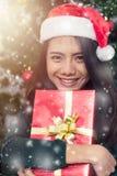 Giovane donna sorridente in cappello dell'assistente di Santa con il contenitore di regalo fotografia stock libera da diritti
