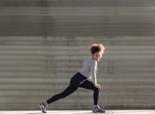 Giovane donna sorridente che allunga i muscoli della gamba Immagine Stock Libera da Diritti
