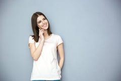 Giovane donna sorridente che comunica sul telefono Immagine Stock