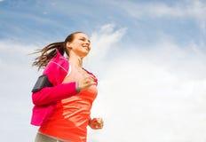 Giovane donna sorridente che corre all'aperto Immagini Stock