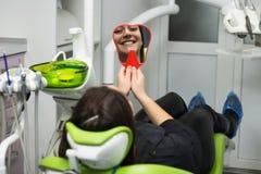 Giovane donna sorridente che esamina riflessione di specchio Fotografia Stock