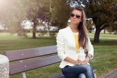 Giovane donna sorridente che gode del suo giorno su un banco nel parco Fotografia Stock Libera da Diritti