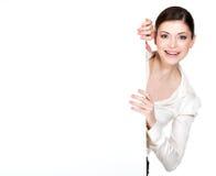 Giovane donna sorridente che guarda dall'insegna in bianco bianca Immagini Stock Libere da Diritti