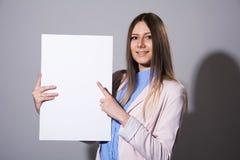 Giovane donna sorridente che indica ad uno strato bianco in bianco Fotografie Stock