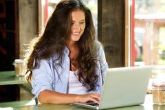 Giovane donna sorridente che lavora al computer portatile al caffè Fotografie Stock