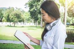Giovane donna sorridente che legge il libro e che si siede sull'erba dentro Immagine Stock Libera da Diritti