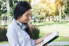Giovane donna sorridente che legge il libro e che si siede sull'erba dentro Fotografia Stock