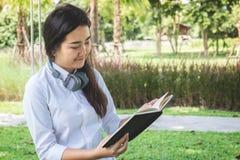 Giovane donna sorridente che legge il libro e che si siede sull'erba dentro Fotografia Stock Libera da Diritti