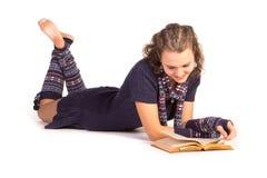 Giovane donna sorridente che legge un libro Immagini Stock