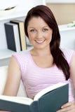Giovane donna sorridente che legge un libro sul sofà Immagini Stock