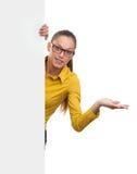 Giovane donna sorridente che mostra carta in bianco Fotografia Stock