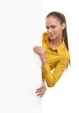 Giovane donna sorridente che mostra carta in bianco Fotografie Stock Libere da Diritti