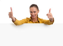 Giovane donna sorridente che mostra carta in bianco Immagine Stock