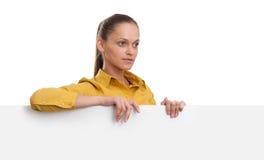 Giovane donna sorridente che mostra carta in bianco Immagini Stock