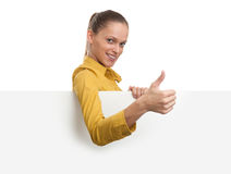 Giovane donna sorridente che mostra carta in bianco Fotografia Stock Libera da Diritti