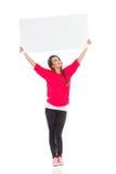 Giovane donna sorridente che mostra cartello bianco Fotografia Stock