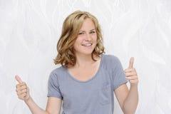 Giovane donna sorridente che mostra i pollici su Immagini Stock Libere da Diritti