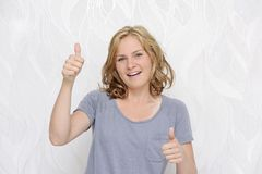 Giovane donna sorridente che mostra i pollici su Immagini Stock
