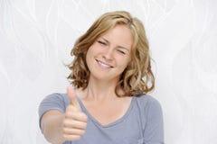 Giovane donna sorridente che mostra i pollici su Fotografie Stock