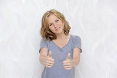 Giovane donna sorridente che mostra i pollici su Fotografia Stock